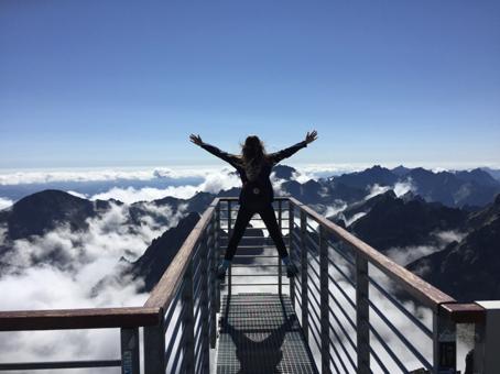 Kvinna uppe bland molnen med utsikt över bergen.
